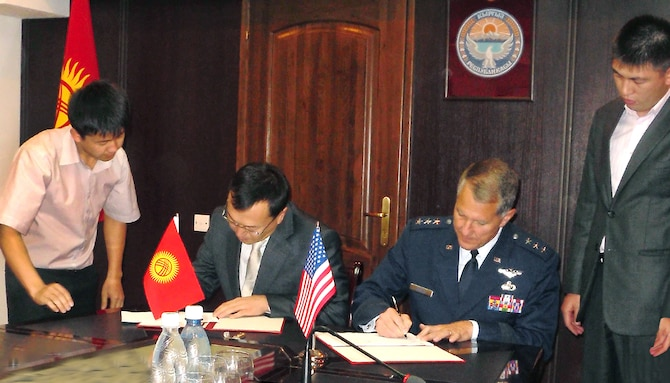 Air Force Electronic Systems Center Commander Lt. Gen. Ted Bowlds and Kyrgyzstani Transportation Minister Erkin Isakov sign an agreement Sept 21 that defines the scope of a critical foreign military sales effort in Kyrgyzstan.  The work will provide the foundation for a robust air traffic control system there.  (Courtesy Photo)