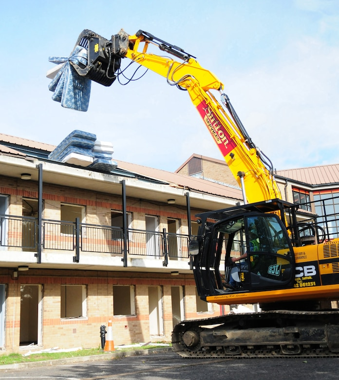 RAF MILDENHALL, England -- A dinosaur-like JCB picks up old mattresses ready to drop them in the dumpster in preparation of demolition of old dormitories here. Contractors are clearing Dorm 212 before it's knocked down. The quality of the Airmen's quarters had deteriorated and had become surplus to requirements. Once demolition is complete, which is scheduled for January 2011, the area will be landscaped. (U.S. Air Force photo/Karen Abeyasekere)