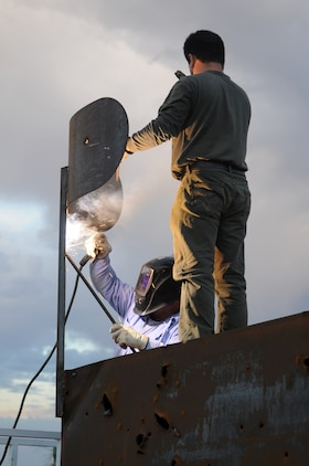 Fernando Godinez, left, TRAX Test Services maintenance crewman, welds the support brace of a fake radar dish on the top of a target shaped like a radar van at the Chocolate Mountain Aerial Gunnery Range, Sept. 29, 2010, as Alex Ribas, TRAX Test Services maintenance crewman, supports the dish. A five-man team traveled the remote areas of the range inspecting and repairing the hundreds of targets in anticipation of the beginning of the Weapons and Tactics Instructor course. TRAX and the station's Range Maintenance section construct and repair more than 300 targets to provide aviators with a realistic training environment before each WTI.