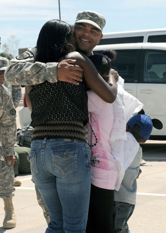 Sgt. 1st Class Timothy Newsome hugs his wife Katrina, daughter Kayla, and son Anthony after returning from a 365-day deployment. (U.S. Air Force photo/Senior Airman Brittany Dowdle)