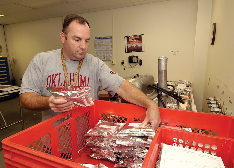 Todd Taylor works in the shipping room of the Bearing Overhaul Shop, preparing finished bearings for customers.  After cleaning and inspecting, bearings are sealed in bags to protect against the smallest contaminants.  (Air Force photo by Margo Wright)