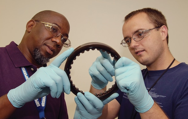 Bearing Overhaul Shop supervisor Melvin Lovings, left, and Stephen Kingham, look over a bearing assembly in the 552nd Commodities Maintenance Squadron facility located in Bldg. 3001. The 11 employees of the Level I shop identify, clean, inspect and process or condemn bearings coming from a variety of engines, missiles and other aircraft components.  (Air Force photo by Margo Wright)