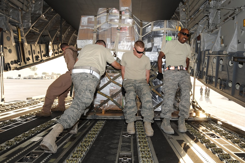 Airmen from the 451st Aerial Port Flight push a cargo pallet during an engine-running offload of a C-17 Globemaster III Sept. 29, 2010, at Kandahar Airfield, Afghanistan. The 451st APF handled more than 26 million pounds of cargo in the month of September. (U.S. Air Force photo by Tech. Sgt. Chad Chisholm/Released)
