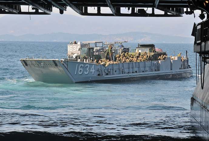 """Marines assigned to the 31st Marine Expeditionary Unit depart the amphibious assault ship USS Essex (LHD 2) aboard a landing craft utility. The unit is conducting Operation """"Field Day"""" on the remote island of Oshima. Operation """"Field Day"""" is a clearing and clean up mission in support of Operation Tomodachi.::r::::n::::r::::n::::r::::n::"""