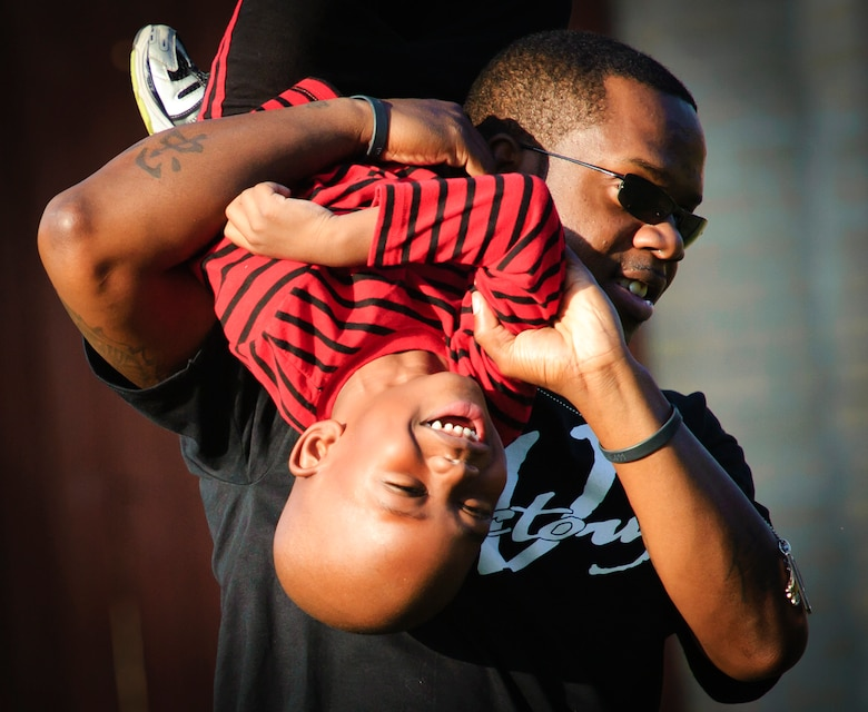 ?Uncle Face? ? or Staff Sgt. Aron Lee ? plays football with Nathaniel in the back yard. Lee got a humanitarian assignment to Lackland AFB, Texas, to help his parents raise Nathaniel after the tragic deaths of the boy?s mom and dad.(Photo by TSgt Samuel Bendet)