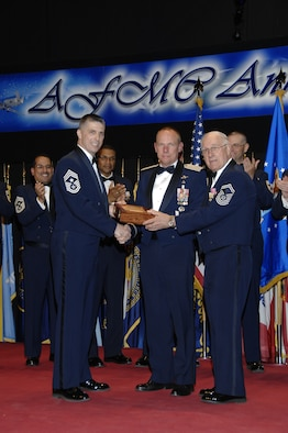 Gen. Donald Hoffman, Air Force Materiel Command commander, stands between AFMC Command Chief Master Sgt. Eric Jaren and former Chief Master Sgt. of the Air Force Sam Parish during the AFMC Enlisted Awards Banquet March 31, 2011. During the banquet, Chief Jaren made a surprise announcement that General Hoffman will be inducted into the AFMC Order of the Sword in October 2011. (U.S. Air Force photo/Ben Strasser)