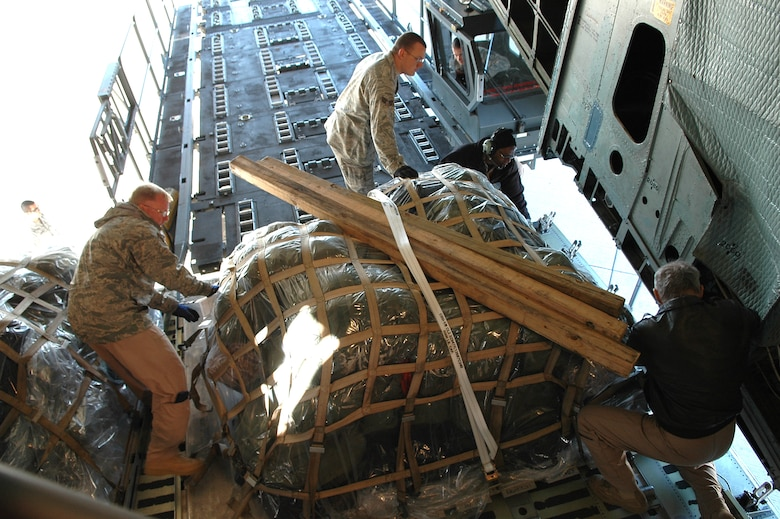 Airmen from the 72nd Logistcs Readiness Squadron and C-5 loadmasters from the 89th Airlift Squadron at Wright Patterson Air Force Base, Ohio, move a pallet from a loader into the cargo bay of a C-5 Globemaster for a 552nd Air Control Wing deployment. (Air Force photo by Micah Garbarino)