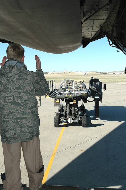 Master Sgt. Dave White, a C-5 loadmaster with the 89th Airlift Squadron at Wright Patterson Air Force Base, Ohio, guides a 72nd Logistics Readiness Squadron vehicle loaded with pallets and driven by 72nd Logistics Readiness Squadron's Staff Sgt. Mike Harrison. The pallet is bound for an undisclosed location where the 552nd Air Control Wing is deployed in support of Operation Odyssey Dawn.  (Air Force photo by Micah Garbarino)