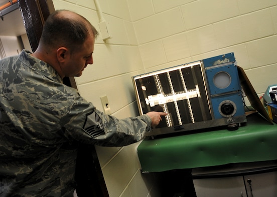 Master Sgt. Chad Shipman, 51st Maintenance Squadron, looks at an X-ray photo of