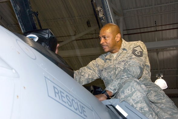 """Master Sgt. Peter Smith, a phase maintenance supervisor at the 162nd Fighter Wing, works on an F-16 Fighting Falcon at Tucson International Airport. Smith, who is a highly regarded mentor among his fellow Airmen, learned a great deal about leadership as a college football player under famed Alabama coach Paul """"Bear"""" Bryant. (U.S. Air Force photo/Master Sgt. Dave Neve)"""