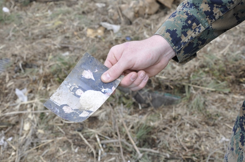 NODA MURA, Iwate, Japan – A U.S. Marine holds up a damaged family photo found in a tsunami-struck area here March 29. Nearly 40 U.S. service members and civilians left Misawa Air Base, Japan, to assist in tsunami cleanup and relief efforts in the village as part of Operation Tomodachi. (U.S. Air Force photo by Senior Airman Joe McFadden/Released)