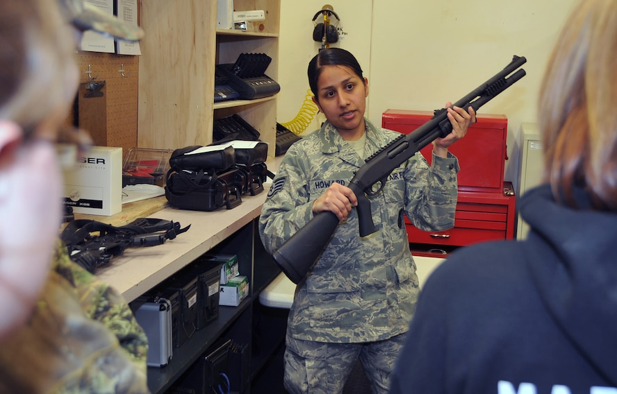OFFUTT AIR FORCE BASE, Neb. -- Staff Sgt. Tracy Howard, NCO in charge of the 55th Security Forces Squadron armory, shows eight students from St. Mary?s High School (Kansas) an M-870 shotgun and explains how security forces Airmen use it inside the armory here March 24. The students visited the armory as part of a base tour. U.S. Air Force Photo by Jeff W. Gates