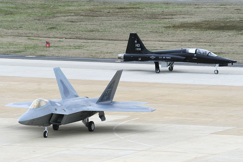 An F-22 Raptor and a T-38 Talon arrive April 1, 2011, at Langley Air Force Base, Va. The T-38 is temporarily assigned to the 1st Fighter Wing to support combat readiness training for the F-22 pilots. (U.S. Air Force photo/Senior Airman Brian Ybarbo)