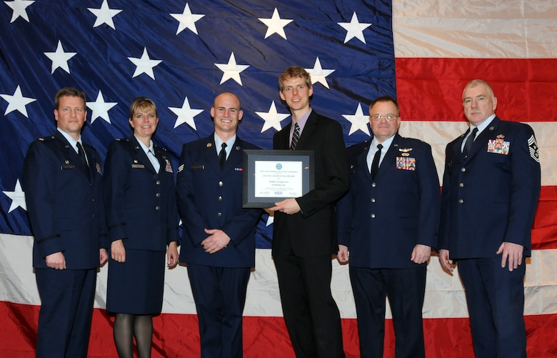 """Kevin Johnson of Tender Loving Care Inc. poses for a group photo with members of the 148th Fighter Wing, Duluth, Minn. while attending a Minnesota Employer Support for the Guard and Reserve Banquet held in Oakdale, Minn.  Johnson was at the banquet to accept the """"Above and Beyond Award"""" recognizing Tender Loving Care Inc. for its support of military employees.  (U.S. Air Force photo by Master Sgt. Ralph J. Kapustka)"""