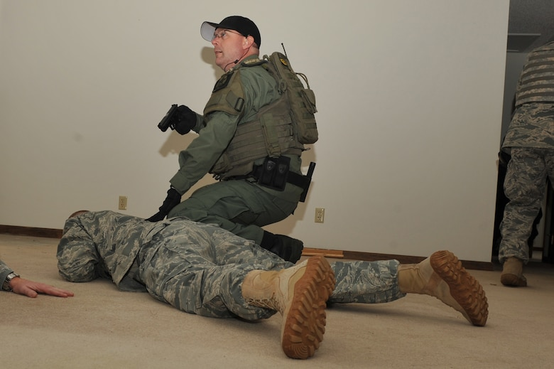 SEYMOUR JOHNSON AIR FORCE BASE, N.C.-- A Duplin County Sheriff's Office special response team member pins down Staff Sgt. Tommy Dailey while searching a room during a training exercise here, April 5, 2011. Sergeant Dailey is playing the role of an assailant to ensure the first responders know how to properly secure aggressors. Sergeant Dailey is a 4th Security Forces Squadron Combat Arms Training and Maintenance instructor and is from Desoto, Ill. (U.S. Air Force photo/Senior Airman Whitney Lambert) (RELEASED)