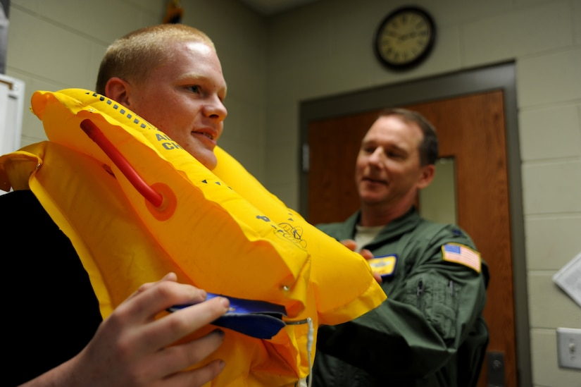 Lt Col Mike Phillips adjusts a life vest that freshman, Cody Frakes was given the oppurtunity to try on during a school visit to Ashley Ridge High School on April 5.  Colonel Phillips is a part of the Air Mobility Command Demonstration team is scheduled to perform an air drop at the 2011 Air Expo on April 8.  Colonel Phillips is a C-17 pilot with the 16th Airlift squadron.  He and Staff Sgt. Scott Skinner, a loadmaster from the 15th Airlift Squadron, explained thier jobs to 9th and 10th grade JROTC students during the school visit.  (U.S. Air Force photo/ Staff Sgt. Nicole Mickle)  (Released)