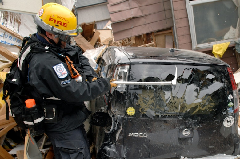 Firefighter Gamble, CA-TF2 breaks a window of a car to search it for tsunami victims in Ofunato, Japan on March 15, 2011. The Los Angeles County Fire Urban Search and Rescue Team, Task Force 2, travelled with the 452nd Air Mobility Wing, March Air Reserve Base, Calif., to the earthquake and tsunami stricken areas of Japan just four days after the devastation.  (U.S. Air Force photo/Technical Sgt. Daniel St. Pierre)