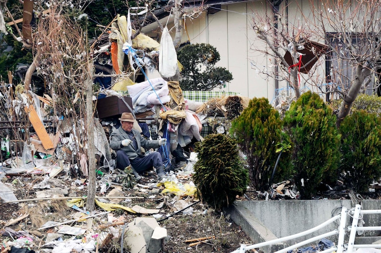 A Japanese man sifts through the aftermath of the deadly tsunami that ripped through his city days earlier.  The Los Angeles County Fire Urban Search and Rescue Team, Task Force 2, travelled with the 452nd Air Mobility Wing, March Air Reserve Base, Calif., to the earthquake and tsunami stricken areas of Japan just four days after the devastation.  (U.S. Air Force photo/Technical Sgt. Daniel St. Pierre)