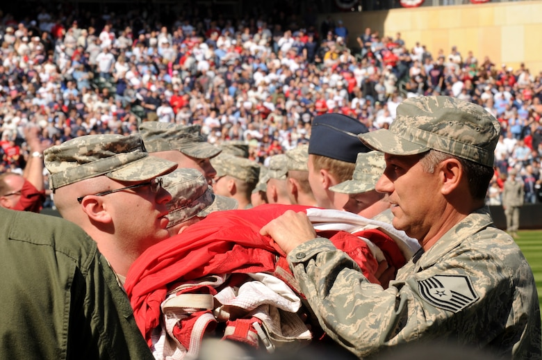 Members of the Minesota Air National Guard and Minnesota Army National Guard unravel a 1600 pound flag held by over 130 Soldiers and Airmen during the Minnesota Twins home opener April 8, 2011 at Target Field in Minneapolis. USAF official photo by Tech. Sgt. Erik Gudmundson