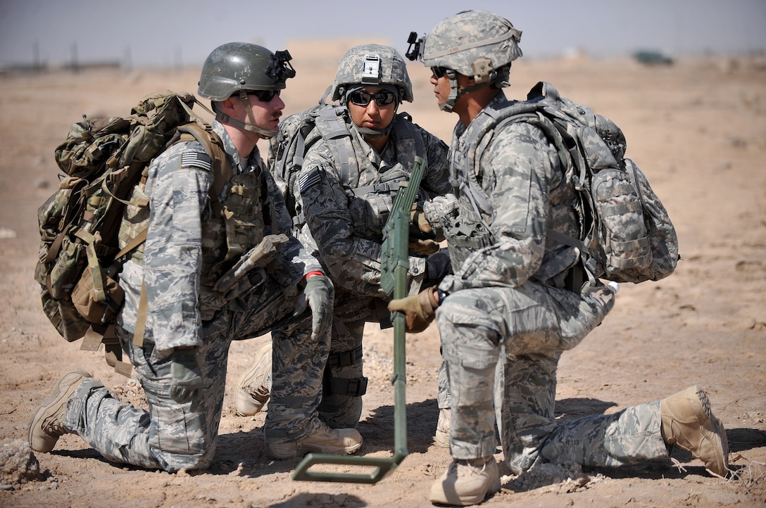 The 407th Expeditionary Operations Support Squadron explosive ordnance disposal team talks together about the scenario at hand during a training exercise March 3, 2010, at Ali Air Base, Iraq. (U.S. Air Force photo by Senior Airman Andrew Lee/Released)