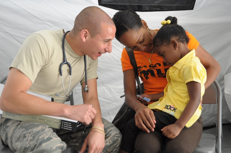 U.S. Air Force Capt. Brian Montenegro, 60th Medical Group Pediatrician, talks to Gabriella Alexander, 3, at Cumuto Barracks in Trinidad and Tobago April 9, 2011. Montenegro is a part of the Expeditionary Medical Support Health Response Team in support of the Allied Forces Humanitarian Exercise/Fuerzas Aliadas or FA HUM 2011. (U.S. Air Force photo by 2d Lt Joel Banjo-Johnson/Released)