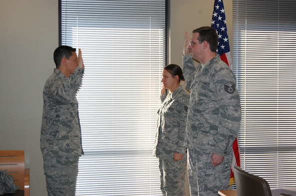 NELLIS AIR FORCE BASE, Nev. -- (Left to Right) Capt. Fernando Ruiz, 706th Fighter Squadron director of information operations, administers the oath of office to Tech. Sgt. Julie Tischbein, 706th FS operations intelligence craftsman, and Tech. Sgt. Matthew Turner, 706th FS cyber systems operator, during their promotion ceremony here March 31. (U.S. Air Force photo/Capt. Jessica Martin)