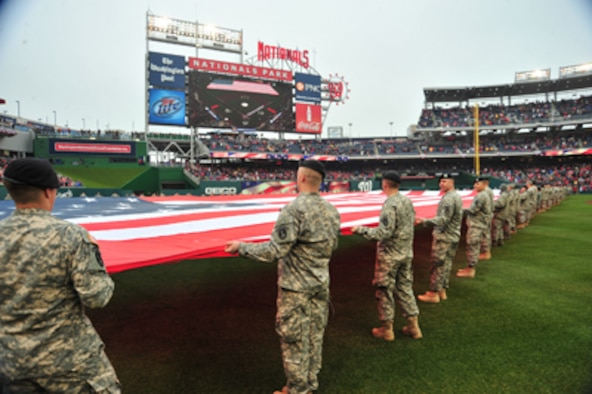 Members of the D.C. National Guard hold a football-field sized American flag on the outfield during pre-game ceremonies for Opening Day at Nationals Park in Washington, D.C. March 31, 2011. U.S. Air Force Photo by Tech. Sgt. Tyrell Heaton