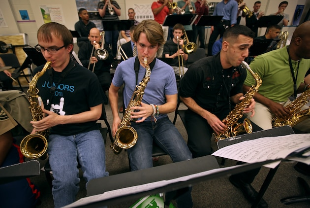 Members of the Marine Corps All Star Jazz Band sit next to band students of Traverse City West High School, Traverse City, Mich., during a clinic April 12, 2011. The All Star Jazz Band is made up of the best 18 Marine jazz musicians, chosen through a audition based selection process, and tours to increase recruiting in the specific Marine Corps District they perform in. The band holds concerts and clinics at high schools and colleges as they travel.