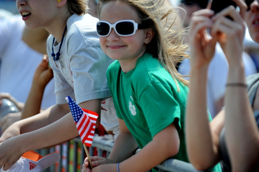 Eight year old Louise Martin waves an American flag as she watches the GEICO skytypers perform during Family Day April 8 at Joint Base Charleston, S.C. The GEICO skytypers performed low-level precision formation flying for nearly 80,000 people at the Charleston Air Expo 2011.  (U.S. Air Force photo/ Staff Sgt. Nicole Mickle)