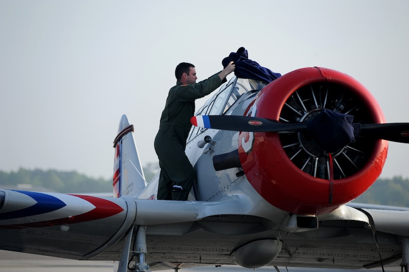 A Charleston Air Expo 2011 volunteer removes the cover off of one of the GEICO Skytypers' SNJ-2 aircraft before their performance on April 9 at Joint Base Charleston, S.C.  GEICO skytypers performed low-level precision formation flying for nearly 80,000 people during the Charleston Air Expo 2011.  (U.S. Air Force photo/ Staff Sgt. Nicole Mickle)