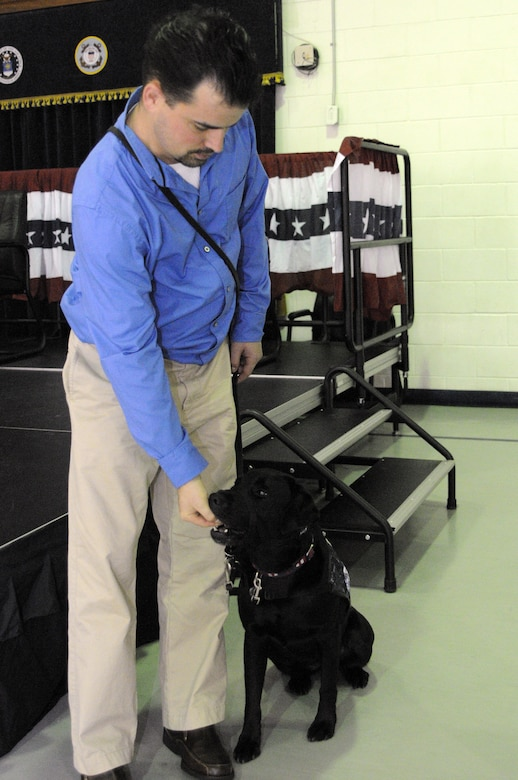 Retired Marine Sgt. Jason Blondin, from Wounded Warrior Battalion East, gives a treat to his newly adopted four-year-old black Labrador Retriever, Eden, which was provided by Carolina Canines for Service and the Naval Consolidated Brig Charleston during a ceremony at NAVCONBRIG, March 31.  The partnership of CCFS and NAVCONBRIG provides highly trained service dogs to wounded warriors.  (U.S. Navy photo/Machinist's Mate 3rd Class Brannon Deugan)