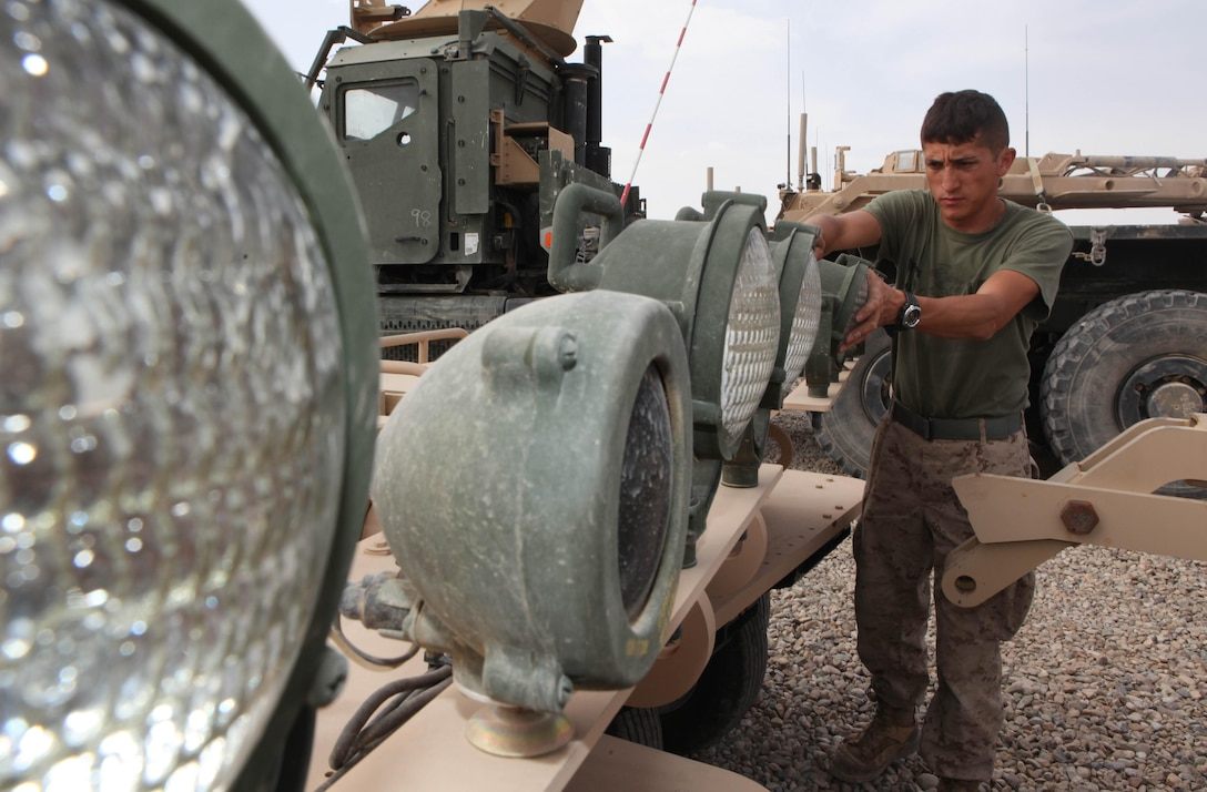 New York resident Pfc. Norberto Ariza adjusts a light on a mine roller April 14. Ariza is a motor transport operator with Regimental Combat Team 8, 2nd Marine Division (Forward). The Motor-T section has received and distributed more than 60 mine rollers since arriving in Afghanistan in December. ::r::::n::::r::::n::::r::::n::