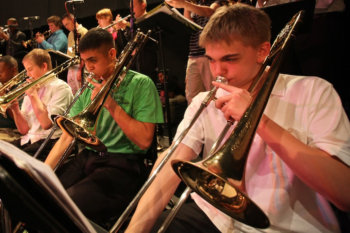 Cpl. Nick Navarro, a trombonist in the Marine Corps All Star Jazz Band, plays with band students to his left and his right at Marquette High School, Marquette, Mich., during a clinic, April 14, 2011. The All Star Jazz Band is made up of the best 18 Marine jazz musicians, chosen through a audition based selection process, and tours to increase recruiting in the specific Marine Corps District they perform in. The band holds concerts and clinics at high schools and colleges as they travel. Navarro is the youngest musician on the the All-Star ensemble.