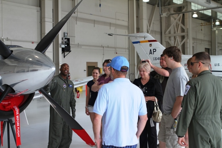NAVAL AIR STATION PENSACOLA, Fla. -- Capt. Julian Venton, 479th Flying Training Group T-6 Texan II instructor pilot, explains the features and capabilities of a T-6 to family members of students in the Combat Systems Officer Course April 14. The tour was a part of the Red Carpet Day prior to the graduation of the first class to undergo combat systems officer training. The graduation will take place April 15. (U.S. Air Force photo/2nd Lt. Charles J. Hopkins IV)