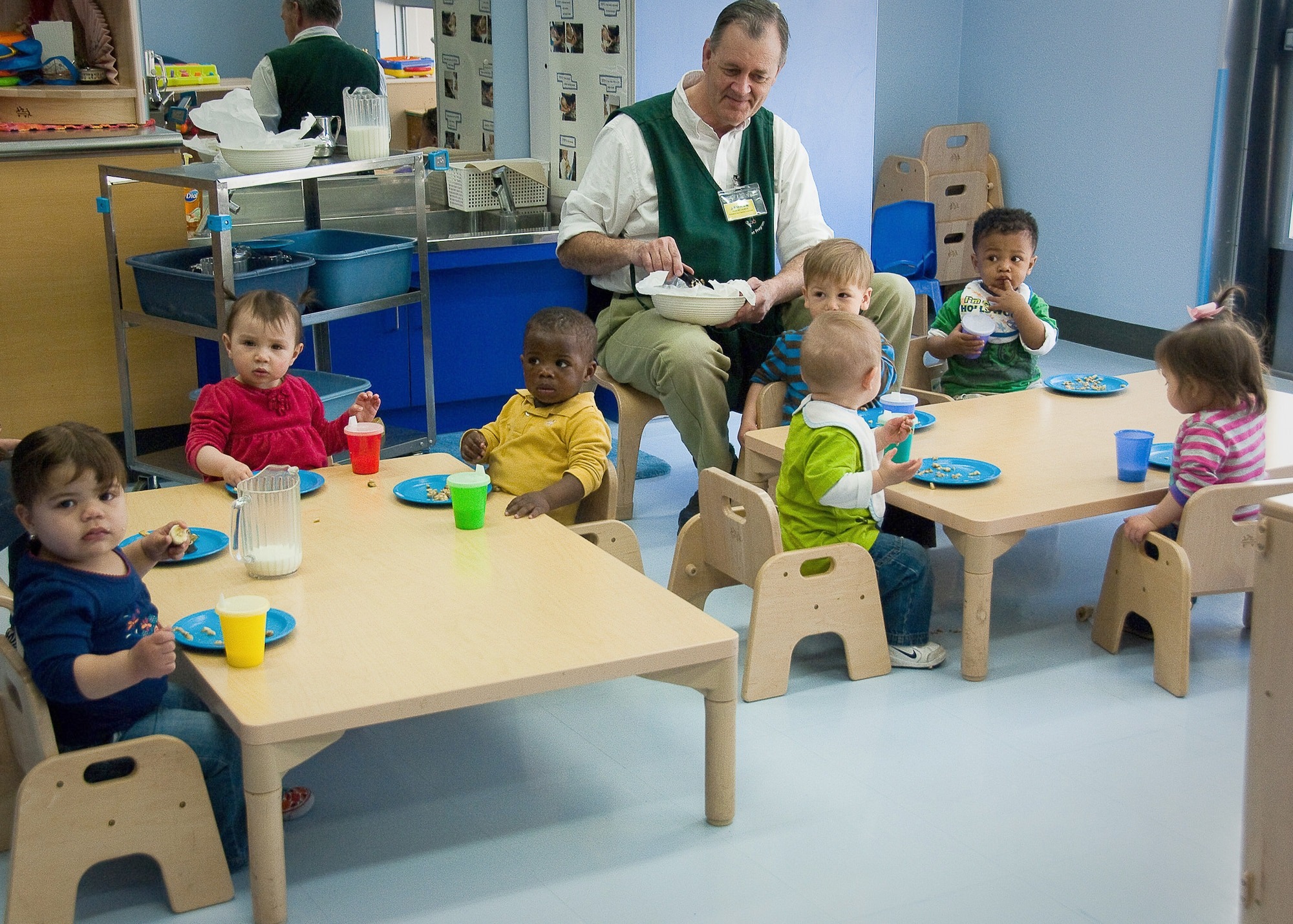 Bob Huber, the pre-toddler room lead at the Yume Child Development Center at Yokota Air Base, Japan, feeds an afternoon snack to children April 12, 2011. Caregivers at Yokota Air Base CDCs work together to continue normal routines with the children by carrying on everyday activities in the aftermath of the earthquake and tsunami. (U.S. Air Force photo/Airman 1st Class Lynsie Nichols)