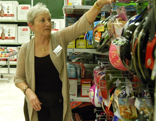 OFFUTT AIR FORCE BASE, Neb. -- Nancy Copada, Offutt Exchange main store manager, adjusts some bike helmets on display in the toy section of the Base Exchange here March 16. Ms. Copada has worked for the Army and Air Force Exchange Service for 26 years and said she loves working for the company. In 2005 she served a seven-month deployment in Iraq supporting U.S. servicemembers. U.S. Air Force photo by Staff Sgt. James M. Hodgman (Released)