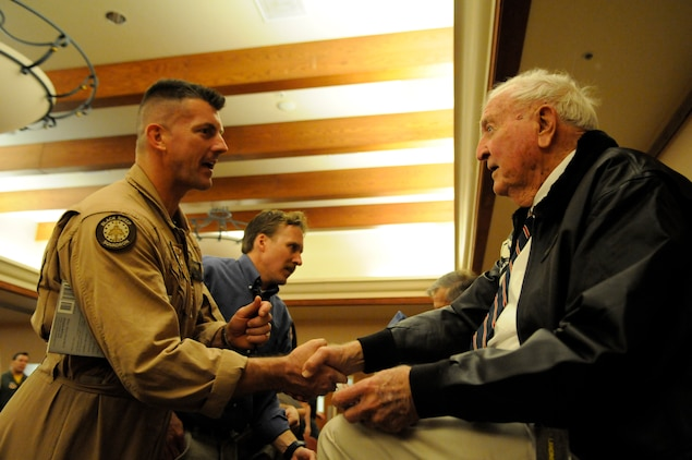 """Harry Johnson, original Marine Attack Squadron 214 pilot, shakes hands with Lt. Col. Gary Roesti, Marine Aircraft Group 13 headquarters element commanding officer, during a dinner for the Black Sheep reunion hosted by the Marine Corps Aviation Association at the Sonoran Pueblo April 14, 2011. Johnson, Jim Hill and Ed Harper, all original Marine Attack Squadron 214 pilots and three of the only five still remaining, attended the event. All served under Medal of Honor recipient and first Black Sheep commanding officer Gregory """"Pappy"""" Boyington during the squadron's first combat deployment in the Pacific in 1943."""