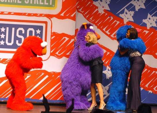 "First lady Michelle Obama and Dr. Jill Biden greet Sesame Street Muppets Telly and Grover while Elmo waits for his hug during a ""Joining Forces"" community event April 14, 2011, in Columbus, Ohio. The event also kicked off the Sesame Street and USO Experience for Military Families, a free traveling tour exclusively for military families. (Defense Department photo/Elaine Sanchez)"