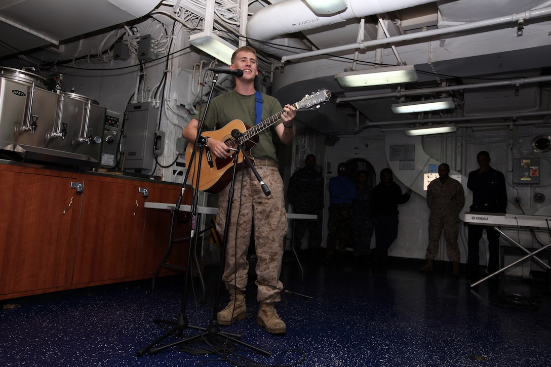 """Corporal Andrew Visscher, a rifleman with Battalion Landing Team, 2nd Battalion, 2nd Marine Regiment, 22nd Marine Expeditionary Unit, and a Bozeman, Mont., native, sings an original song during USS Bataan's """"Saturday Night Alive"""" talent show, April 16, 2011.  The Marines and sailors of the 22nd Marine Expeditionary Unit are currently deployed with Amphibious Squadron 6 aboard the USS Bataan Amphibious Ready Group and will continue to train and improve the MEU's ability to operate as a cohesive and effective Marine Air Ground Task Force.  The 22nd MEU is a multi-mission, capable force, with approximately 2,200 Marines and sailors, and comprised of Aviation Combat Element, Marine Medium Tilt Rotor Squadron 263 (Reinforced); Logistics Combat Element, Combat Logistics Battalion 22; Ground Combat Element, BLT 2/2; and its Command Element."""