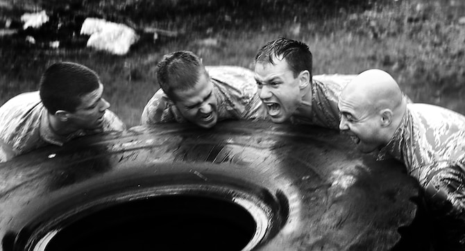 Members of the Air Force Sandhurst team try to flip a large tire across roughly 50 yards during the Sandhurst Competition Saturday, April 16, 2011 at the U.S. Military Academy, N.Y.  The competition requires each team to perform a series of challenging military tasks along a 7-mile route, and compete in a marksmanship competition.  The team only had a rough idea of what to train for as most of the challenges were kept secret until the day of the event.  (U.S. Air Force photo/Staff Sgt. Raymond Hoy)