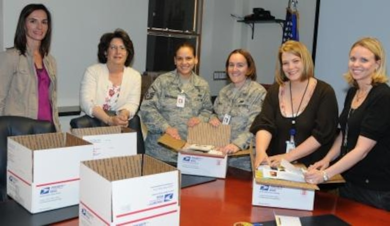 Air Force Operational Test and Evaluation Center members gather with members of the AFOTEC Key Spouse Program to put together quarterly care packages for deployed team members. (Left to right) Denise Eck, Anita Eichhorn, Master Sgt. Susan Maldonado, Technical Sgt. Maria Smith, Brandi Miller, and Stephanie Griffin.