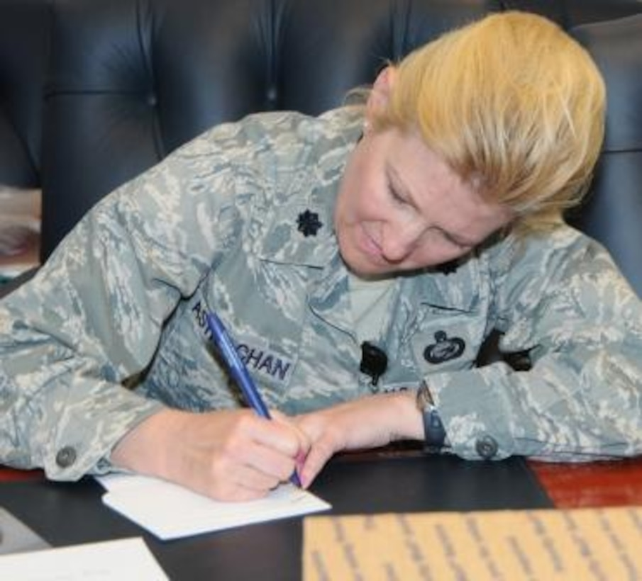 Lt. Col. Juliana Astrachan, Air Force Operational Test and Evaluation Center Director of Manpower and Personnel, writes a personal note to a deployed team member to be included in a care package.