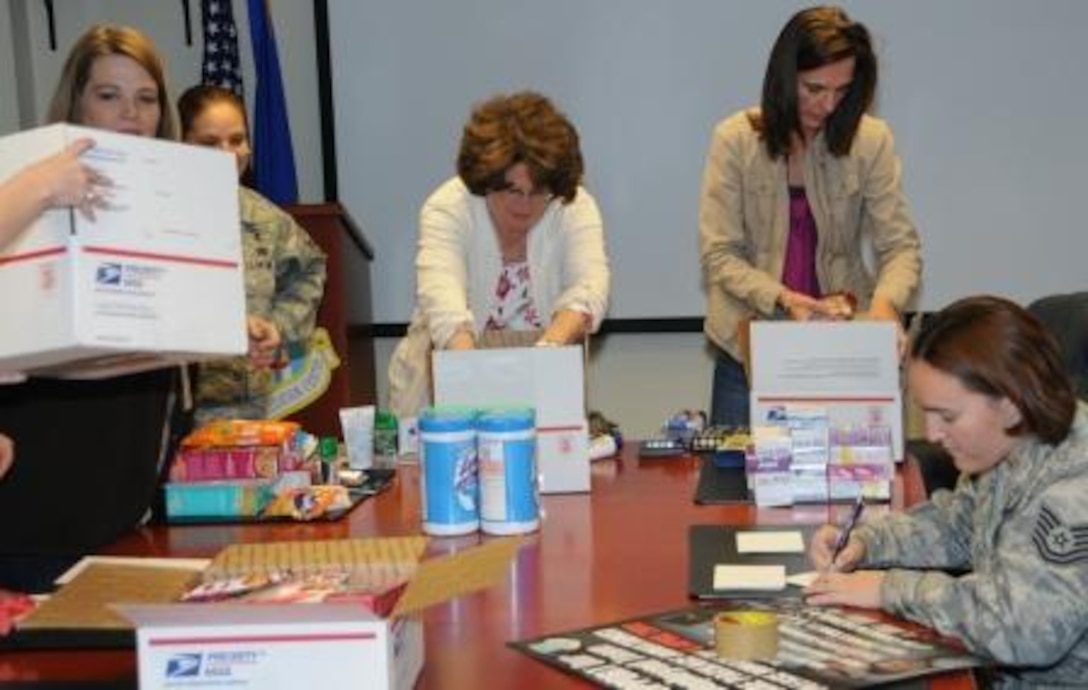 Air Force Operational Test and Evaluation Center members fill care packages for deployed members. (Center left) Anita Eichhorn, wife of AFOTEC Commander Maj. Gen. David Eichhorn, and (center right) Denise Eck, wife of AFOTEC Vice Commander Col. James Eck, help put packages together.