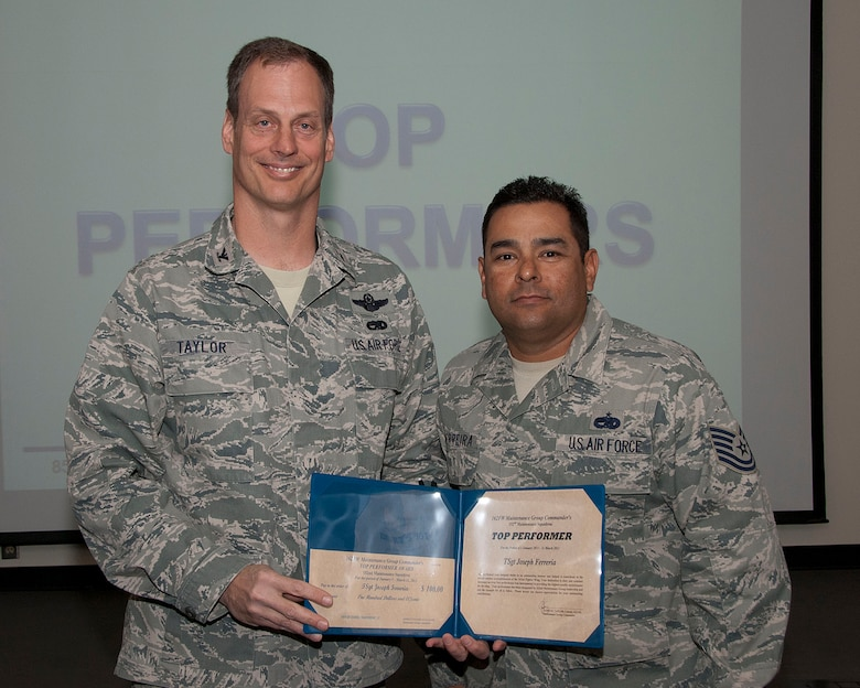 Col. James Taylor (left) presents Tech. Sgt. Joseph Ferreira the Top Performers Award for his work with 152nd Fighter Squadron.  (U.S. Air Force photo/Master Sgt. David Neve)