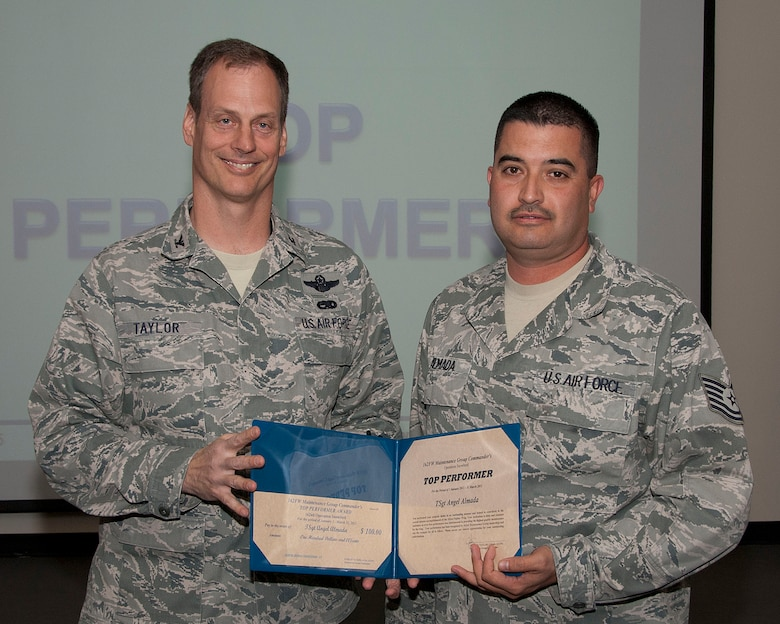 Col. James Taylor (left) presents Tech. Sgt. Angel Almada the Top Performers Award for his work with Operation Snowbird.  (U.S. Air Force photo/Master Sgt. David Neve)