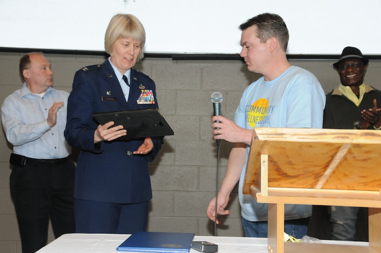 U.S. Air Force Col. Penny Dieryck, commander of the 148th Fighter Wing's Mission Support Group, is seen accepting the Community Champion Award on behalf of the 148 FW, Duluth, Minn., April 16, 2011. The Community Champion Award, presented by Dr. Anthony Macioce of Associated Chiropractic, was given to the 148 FW for continued unselfish commitment to serving the needs of the local community. (U.S. Air Force photo by Senior Airman Sarah C. Hayes)