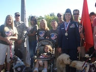 """Brig. Gen. Pamela Milligan, Vice-Commander, 4th Air Force, Air Force Reserve Command, March Air Reserve Base, Calif., poses with members of """"Pawz for Wounded Veterans,"""" at the 6th annual """"Salute to Veterans Parade"""" in downtown Riverside, Calif., April 16, 2011.  """"Paws for Wounded Veterans"""" is an organization that provides service dogs free of charge to those who have been wounded during military service and require the help of an assistance dog.  General Milligan was a member of the reviewing party during the 132-unit parade, which was themed """"Honoring Those Who Have Sacrificed"""" and featured participants from military units from across southern California."""