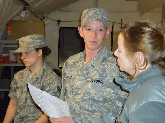 Senior Airman Christina N. Muniz and Staff Sgt. Christopher M. Jones, both from the 103rd Force Support Squadron, 103rd Airlift Wing, Conn. Air National Gurad, give a status report for appropriated fund/nonappropriated fund operations to Lt. Col. Ann C. Ware, 103rd Force Support Squadron commander, during a combat training exercise March 24, 2011, at Dobbins Air Reserve Base, Ga. A team of 15 Connecticut Guardsmen deployed with members of the 104th FSS and MacDill AFB where they focused on wartime/contingency operations relative to a force beddown.  (Photo courtesy of Master Sgt. Melissa A. Letizio)