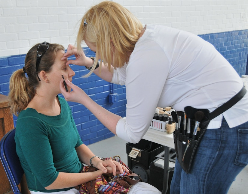 Emilia Tynan, a veteran and wife of Master Sgt. Jeffrey Tynan 628th Logistics Readiness Squadron first sergeant, receives a makeover from volunteer Kindall Crawford, April 19, at Armory Park in North Charleston, S.C. (U.S. Air Force photo /A1C Jared Trimarchi)