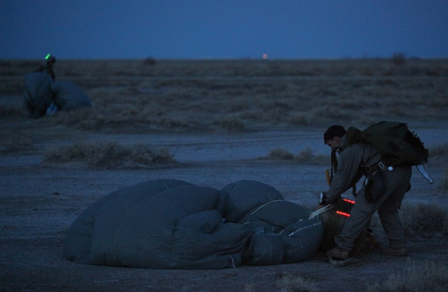 Marines with U.S. Marine Corps Forces, Special Operations Command, pack up their parachutes after conducting a High Altitude, High Opening jump at dusk as part of a Double-Bag Static-Line parachute course in Wendover, Utah, April 9 - 21. The course was taught by personnel from the 2nd MSOB paraloft and the Airborne Mobile Training Team, and is designed to give Marines a basic understanding of HAHO operations.